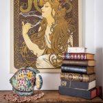 Kútik s obrazom Alfonza Muchu, dekoráciou ryby a knihami.