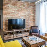 Obývačka v industriálnom štýle so stolíkom a TV stolíkom z dreva a kovu, so žltou sedačkou, koženým kreslom a tehlovou stenou.