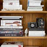 Drevené police s knihami a starými fotoaparátmi.