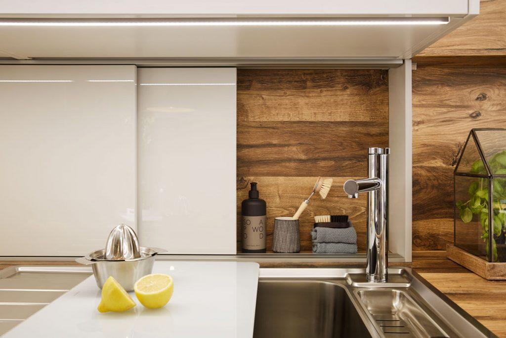 Úložný priestor za kuchynským drezom v podobe úzkej skrinky so zásuvnými dvierkami.