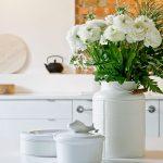 BIela váza s ružami a biela nádoba s rybou na poklope.