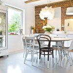 Minimalistická kuchyňa v drevenici s tehlovou stenou, zariadená bielou kuchynskou linkou, jedálenským stolom so stoličkami a starodávnym bielym príborníkom.