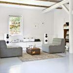 Minimalistická obývačka s dizajnovými sivými kreslami, bielymi trámami a bielym nábytkom.
