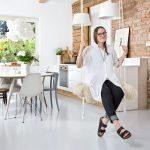 Dizajnérka Asia na hojdačke zavesenej v kuchyni v minimalistickom štýle, s tehlovou stenou a bielym nábytkom.