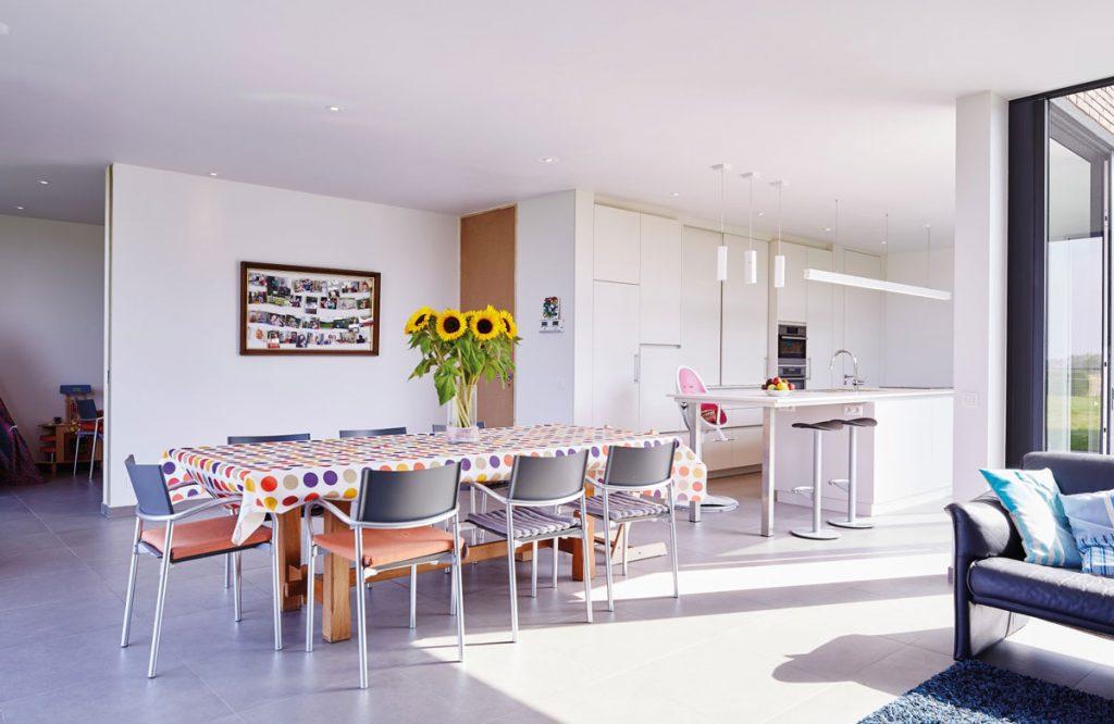 Biela moderná jedáleň s kuchyňou v rodinnom dome.