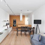 Minimalistický interiér obývačky prepojenej s jedálňou a kuchyňou, s dreveným nábytkom bez úchytiek, v neutrálnych farbách.