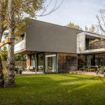 Moderný rodinný dom s nenáročnou prírodnou záhradou s listnatými stromami.