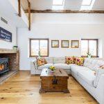 Obývačka vo vidieckom štýle v storočnom gazdovskom dome, s bielou sedačkou, pieckou a starou truhlicou ako stolíkom.