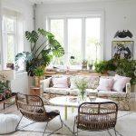 Boho obývačka so sedačkou s potlačou ruží, prírodnými kreslami, okrúhlym stolíkom, kobercom v smotanovej farbe a rôznymi druhmi rastlín.