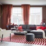 Riešenia pre zmenu v interiéri: Obývačka so sivou sedačkou, páskovaným červenobielym kobercom a smotanovým kreslom.