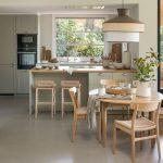 Kuchyňa v neutrálnom zemitom odtieni s drevenými barovými stoličkami, dreveným oválnym jedálenským stolom a vypletanými stoličkami a dizajnovým lustrom.