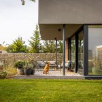 Moderný rodinný dom s terasou so sedením a kvetinami, gabionovým plotom a nenáročnou prírodnou záhradou.