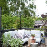 Terasa rodinného domu s výhľadom do záhrady. Na terase je sedenie, stolíky z pňov stromov a nadrozmerné kvetináče s rastlinami.