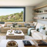Obývacia miestnosť v prírodnom štýle s rohovými oknami, neutrálnou svetlou sedačkou, dreveným stolíkom a troma policami pozdĺž steny.