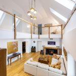 Obývačka v rodinnom dome zariadená vo vidieckom štýle so svetlou L-kovou sedačkou, starou truhlicou ako stolíkom, starožitným stolíkom a s krbom