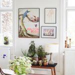 Interiér so stolíkom, na ktorom je váza s rezanými kvetmi, lavicou s kvetinami a bodkovanou lampou a obrazmi s prírodnými motívmi.