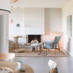 Interiér ladený do neutrálnych farieb s krbom, studenomodrým kreslom, prírodným pleteným kobercom a stolíkmi z prírodných materiálov.