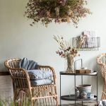 Interiér s prírodným kreslom, stolíkom a závesnou dekoráciou zo sušených kvetov.