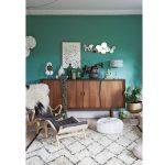 Interiér so zelenou stenou, s retro komodou, na ktorej sú kvety a rôzne dekorácie, s dreveným kreslom, taburetkou, kobercom s geometrickým vzorom.