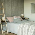 Spálňa v neutrálnych tónoch s jednoduchou posteľou, nočným stolíkom riešeným zavesením na rebrík a prírodným pleteným kobercom.