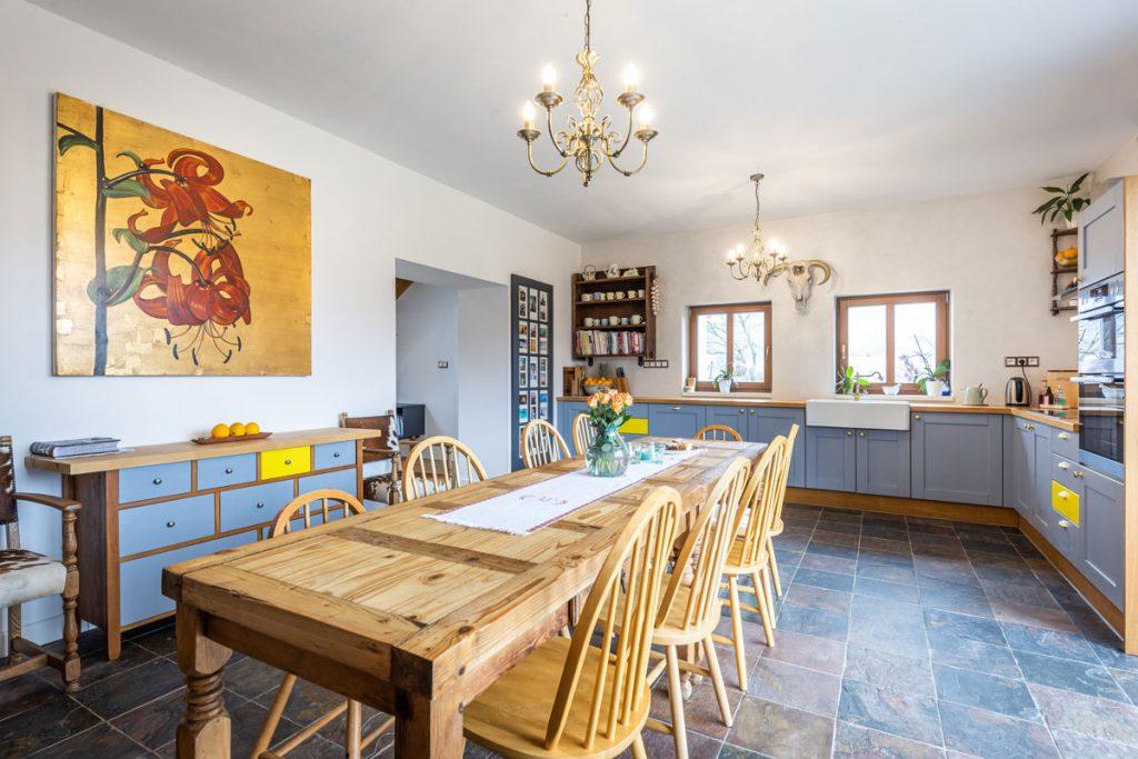 Kuchyňa vo vidieckom štýle s kuchynskou linkou v sivom odtieni a so žltým akcentom na niektorých šuflíkoch, s jedálenským stolom zloženým z dvoch kusov, stoličkami a s podlahou vo vzhľade kameňa