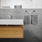 Minimalistická kúpeľňa s umývadlom, dubovou skrinkou a tmavosivou mozaikou s kontrastným škárovaním.