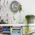 Príručná knižnica vyrobená z dvoch priečok s knihami a vázami s kvetinami.