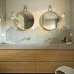 Kúpeľňa s neutrálnym obkladom, okrúhlymi zrkadlami a skrinkou s umývadlom.