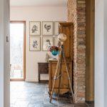 Interiér so starodávnou drevenou vitrínou opretou o tehlovú stenu, za ktorou je schovaná chladnička, s kresbami od Miroslava Matuščina