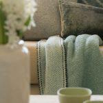 Detail na textílie v neutrálnych farbách, kvetinu a misky.