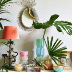Kútik so zrkadlom v tvare ananásu, lampou s opicami a farebnými vázami s kvetom monstery a palmy.