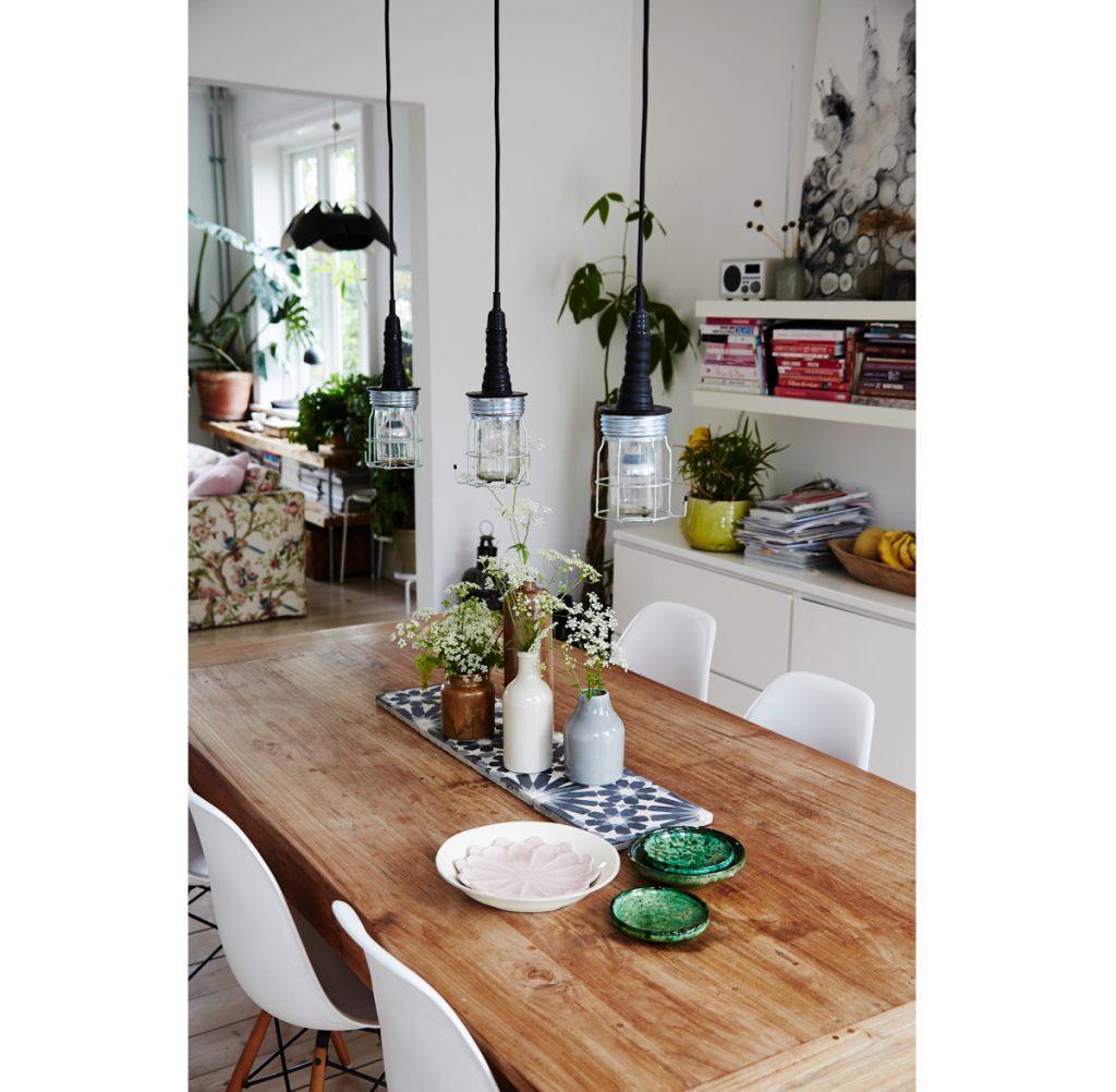 Interiér s rozkladacím jedálenským stolom s vázami s kvetmi, stoličkami, knižnicou a troma svietidlami.