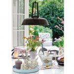 Stôl upravený na jarné stolovanie s keramikou s motívom čerešní, s kvetinovým džbánom, vázou v tvare ľudskej hlavy a textíliami.