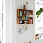 Otvorené poličky s riadmi a dózami a rôzne drevené lopáriky zavesené na stene.