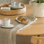 Detail jedálenského stola s textíliou, nádobou s kvetom, pleteným podnosom a šálkami.
