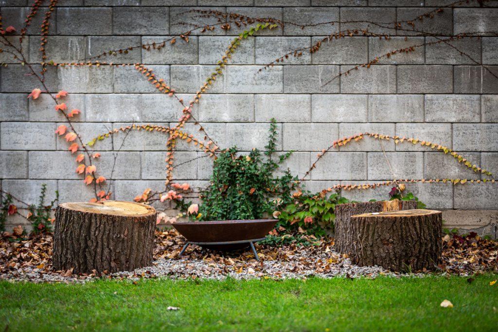 Jednoduché záhradné ohnisko vytvorené zo štrkovej plochy, na ktorej stojí kovové ohnisko a dubové pne na sedenie.