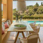 Krytá terasa dovolenkového domu s jedálenským dreveným stolom, ratanovými stoličkami a výklenkom využívaným na sedenie s výhľadom na bazén a okolitú krajinu.