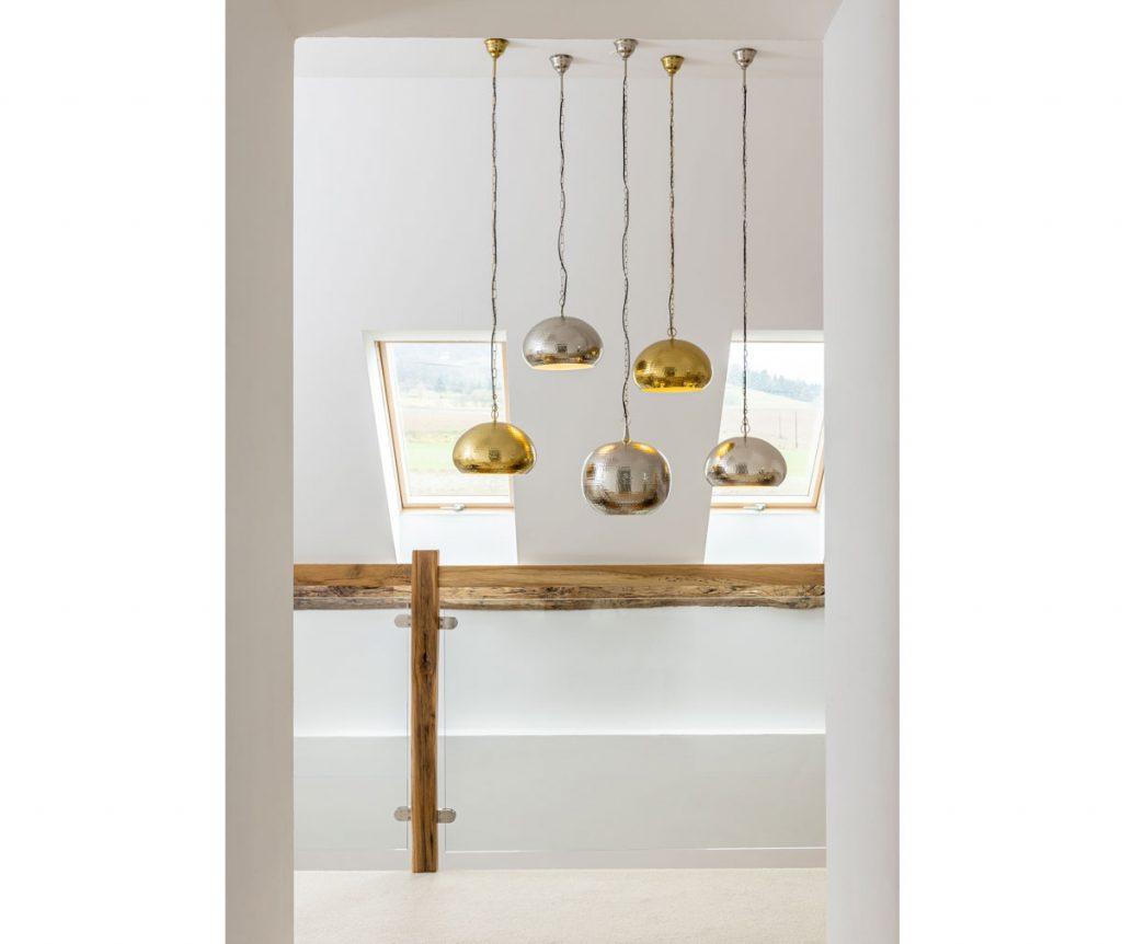 Pätica zlato-strieborných lustrov visiaca pred galériou