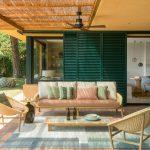 Krytá terasa dovolenkového domu so sedením z prírodných materiálov a posuvnými drevenými okenicami, ktoré chránia interiér domu pred slnkom