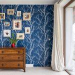 Spálňa s tapetou stromov, s drevenou komodou a obrazmi, s tajnými dverami do šatníka v stene