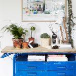 Vintage stolík modrej ošúchanej farby s rastlinami a lampou.