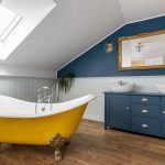 Kúpeľňa v podkroví so zrenovovanou žltou vaňou na zvieracích nožičkách a modrou skrinkou s dvoma umývadlami