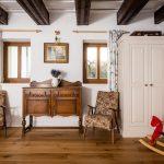 Hosťovská izba v štýle starého Anglicka so starodávnou zdobenou komodou, kvetinovými kreslami, bielou skriňou, hojdacím dreveným koníkom a priznanými drevenými trámami na strope