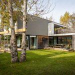 Rodinný dom s nenáročnou záhradou slúžiacou na oddych, s listnatými stromami a hojdačkou.