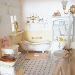 Miniatúra kúpeľne s vaňou, toaletou, umývadlom a skrinkami v domčeku pre bábiky.