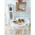 Miniatúrny jedálenský stôl so stoličkami, hodinami a obrazom v domčeku pre bábiky.