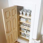 Miniatúra komory s porcelánovými riadmi v domčeku pre bábiky.