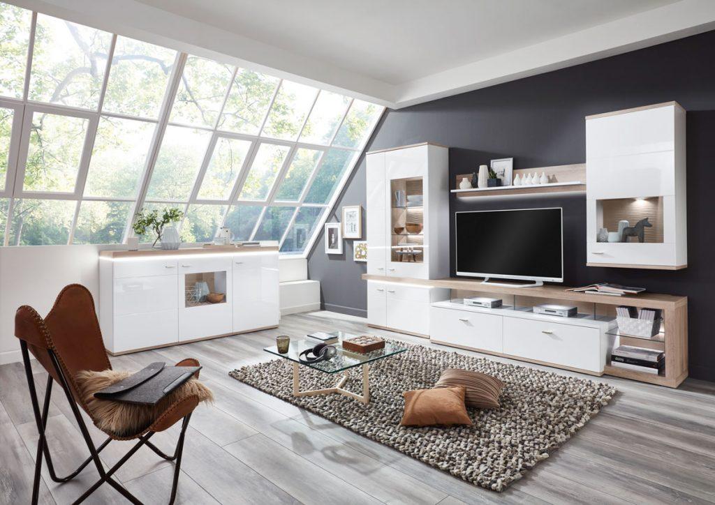 Obývačka v podkroví s lesklou TV stenou s vitrínami, kobercom a koženým kreslom na železnej konštrukcii.