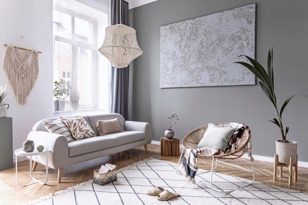 Ratan v interiéri: Obývačka v natur štýle so sivou pohovkou, svetlým kobercom s geometrickým vzorom, ratanovým kreslom, ratanovým tienidlom a makramé závesnou ozdobou.