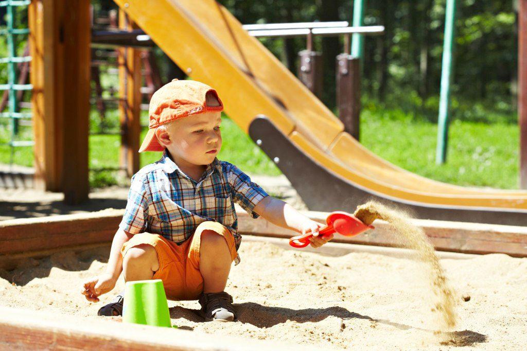 Ako osadiť stĺpiky hracej veže do betónu: dieťa hrajúce sa na ihrisku